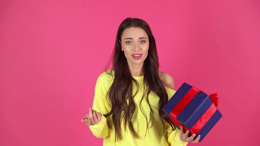 Studio shoot of beautiful upset young woman holding gift box and showing thumb down isolated on crimson | Shutterstock HD Video #1026795251