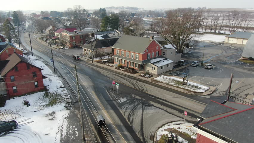 Aerial shot - Following Amish buggy driving through rural town. Shot in Intercourse, PA in wintertime. A beautiful snow covered town with farms, meadows, farmlands and a small village center.