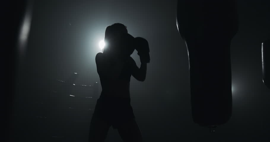 Silhouette of young woman training with a punching bag in a boxing club. Slow motion. Darkness background #1026798824