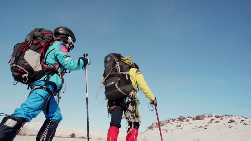 The group of climbers slowly go through the snow, with backpacks behind the back. Travel in snow-covered expanse and the beautiful nature | Shutterstock HD Video #1026807002
