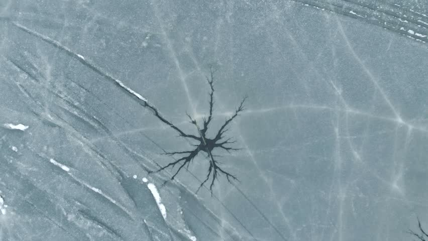 Dutch frozen lake. Star shaped cracks in ice. Cinematic deep crack unique pattern. Winter season. Aerial Drone with zoom out of frozen lake.