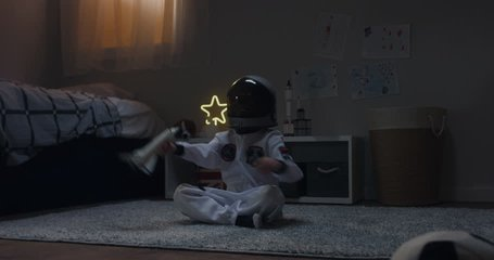 Cute little kid boy wearing astronaut suit playing with toy shuttle space ship rocket at home, bedroom interior evening shot. 4K UHD RAW FOOTAGE