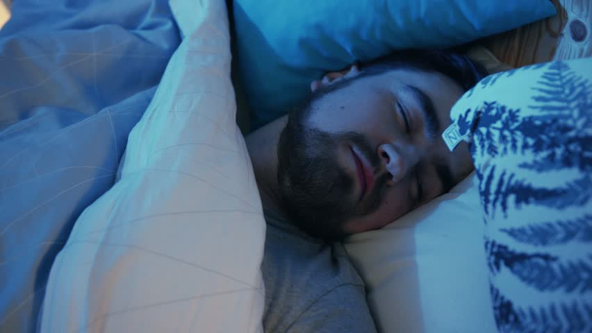 Close-up footage of sleepy young man laying on bed waking up to noise behind wall. Three o'clock in the morning. Night. Indoors. Dream.? | Shutterstock HD Video #1026837644