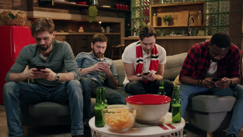 Group of male friends actively using phones. Four people totally focused on their smartphones sitting on couch at home. Attractive men hanging out at home, drinking beer while using their smartphones