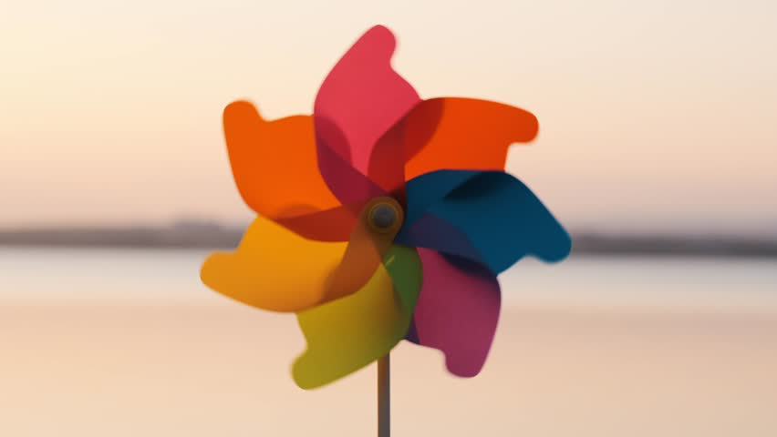 Plastic pinwheel rotate colored with blowing wind stands on sand by sea against the smooth surface of the sea and bright pink sunset. Toy mill on the beach. Large disk of the sun. Copy space. Relax