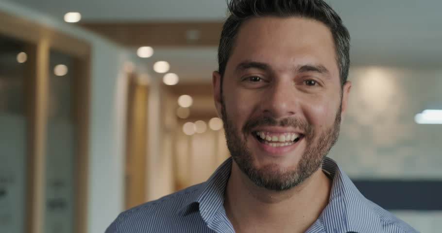 Portrait of confident hispanic businessman looking at camera in office. Young latino business man at work. Happy caucasian manager smiling. Slow motion | Shutterstock HD Video #1026840581