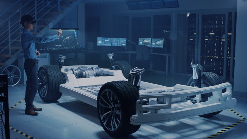 Automotive Engineer Working on Electric Car Chassis Platform, Using Augmented Reality Headset. In Innovation Laboratory Facility Concept Vehicle Frame Includes Wheels, Suspension, Engine and Battery. #1026842780