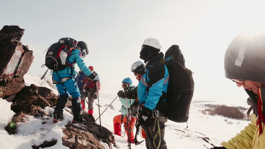 Experienced climbers stopped for a rest on top of the snow-capped mountains, relax and translate breath | Shutterstock HD Video #1026843086
