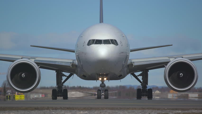 Oslo airport norway - ca april 2019: huge airplane boeing 777 Thai Airways taxiway front view moving towards camera low angle view