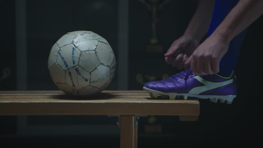 Soccer player tying his football boots in locker room