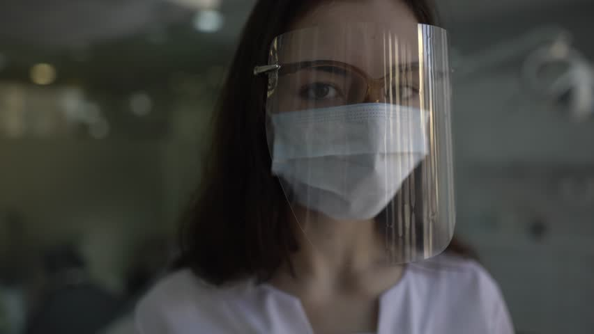 Close-up portrait of young female doctor who is wearing a dental shield, rounded around her face, from a frontal perspective to protect her glasses and eyes. Camera is slowly sliding.