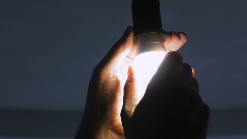 In a dark room, a man replaces an electric energy-saving lamp with a new LED lamp.