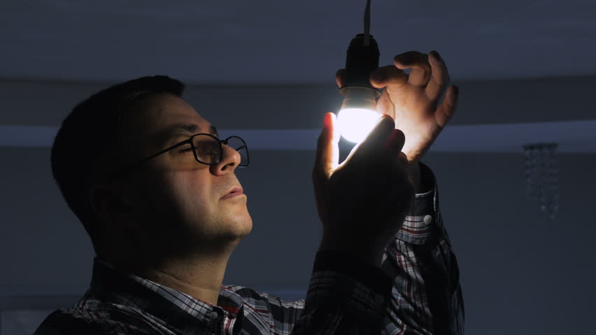 In a dark room, a man replaces an electric energy-saving lamp with a new LED lamp. | Shutterstock HD Video #1026854984