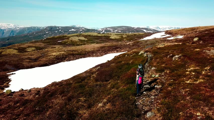A drone flight following a couple carrying big backpack hikes through dry trail, with snow patches in few paces. High mountains in the back covered with snow. Beautiful day for a trek.  | Shutterstock HD Video #1026870332