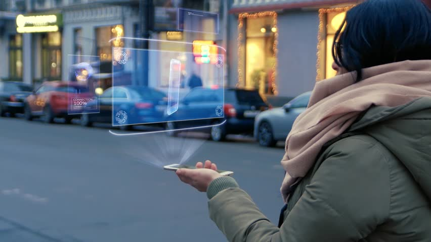 Unrecognizable woman standing on the street interacts HUD hologram with smartphone. Girl in warm clothes with a scarf uses technology of the future mobile screen on background of night city Royalty-Free Stock Footage #1026870647