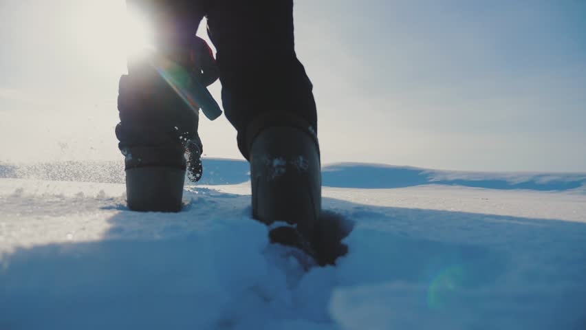 Teamwork. men tourists climbing walking top mountains rocks peak group team sunlight silhouette on snow feet winter snow trip. slow motion video. people teamwork business travel the silhouette