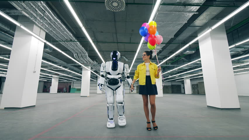 A woman holds balloons in hand while walking in a room with cyborg. | Shutterstock HD Video #1026880409
