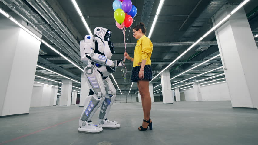 Modern robot receives many balloons from a girl. | Shutterstock HD Video #1026880418
