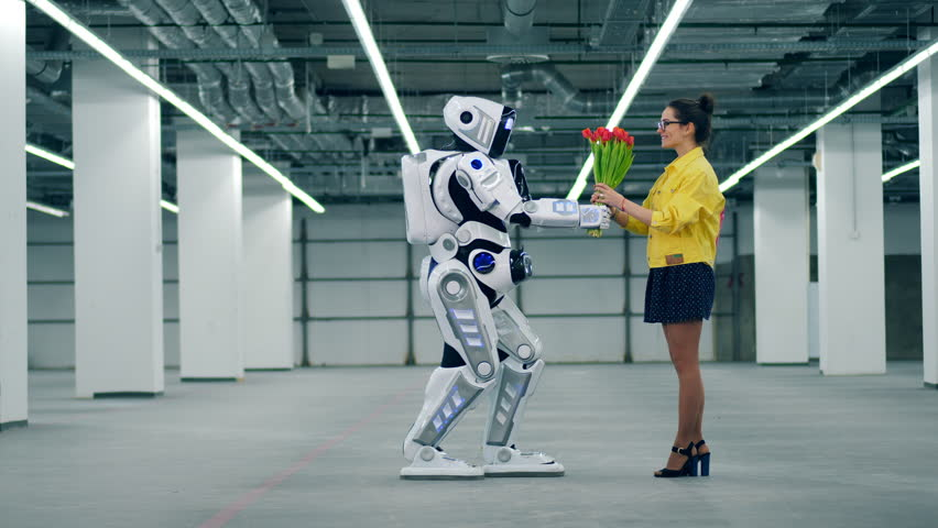 One droid gives a bouquet of red tulips to a woman and she hugs it. | Shutterstock HD Video #1026880433