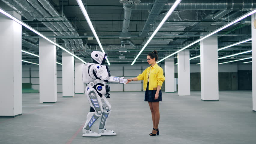 White robot and a woman touch hands, greeting each other. | Shutterstock HD Video #1026880460