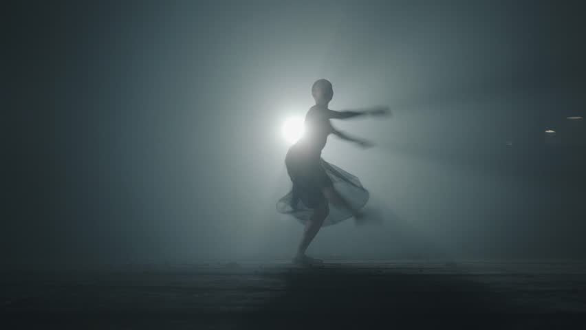 Diligent young graceful ballerina dancing elements of classical ballet in the dark with light and smoke on the background. Beautiful young ballerina in darkness. Ballet practice in studio. | Shutterstock HD Video #1026881546