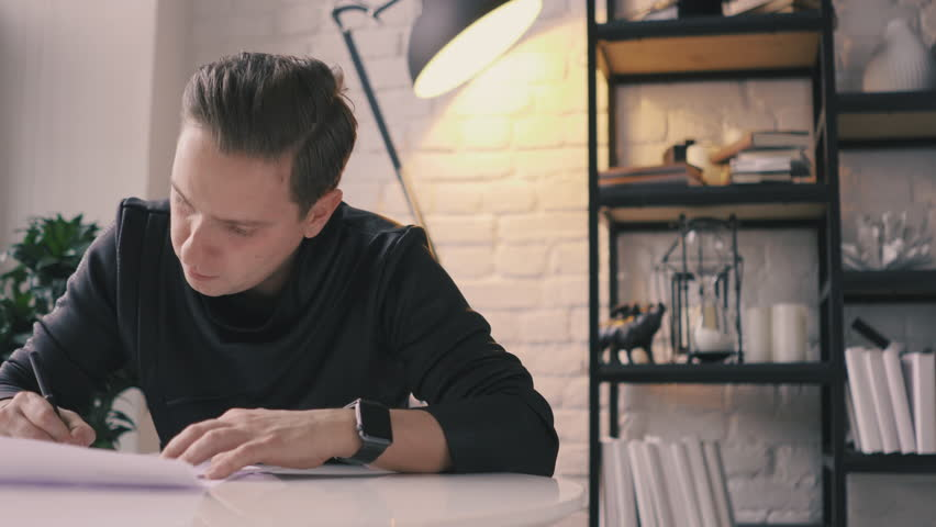 Satisfied white young man in a black jacket sits at a white table in the office against the background of a white wall and writes on paper, then looks out the window. He signs a contract or letter #1026884768