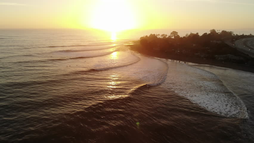 Aerial drone shot over Rincon Point surf break with ocean waves and surfers riding during sunset on the beautiful California coastline. | Shutterstock HD Video #1026884906