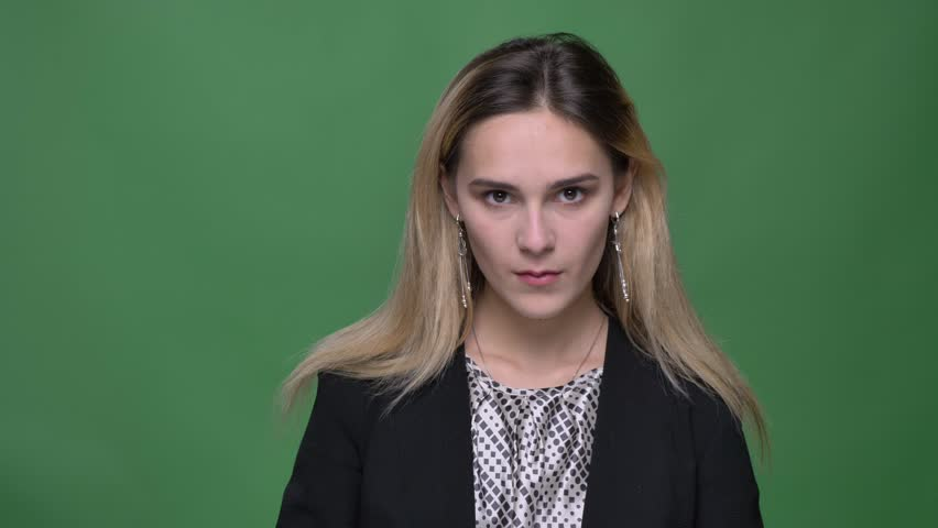 Closeup shoot of young attractive hipster caucasian female looking straight and posing in front of the camera with background isolated on green | Shutterstock HD Video #1026885314