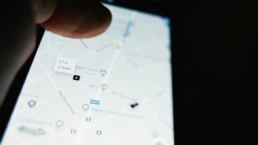 Brussels, Belgium - Circa 2019: Man POV holding iPhone smartphone running UBER peer-to-peer ridesharing app following trip share my trip during a ride ETA less than 1 minute