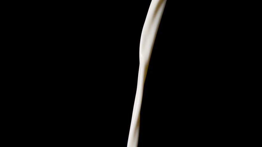Macro shot of pouring milk in slow motion in front of black background.
