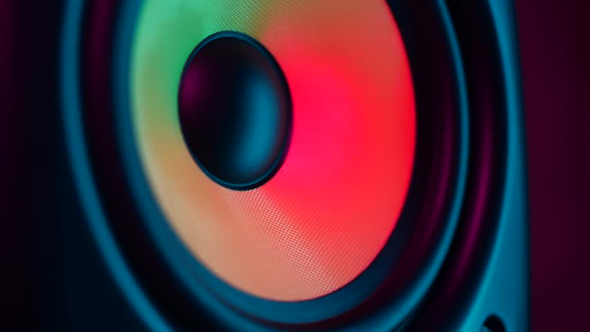 Close up of colorful loud bass speaker vibration on black background