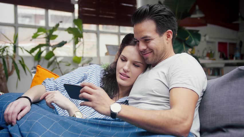 Cute Hispanic couple chilling in cosy living room, watching video in YouTube family blogger channel using smart phone device, enjoying entertainment leisure content, spending | Shutterstock HD Video #1026888944