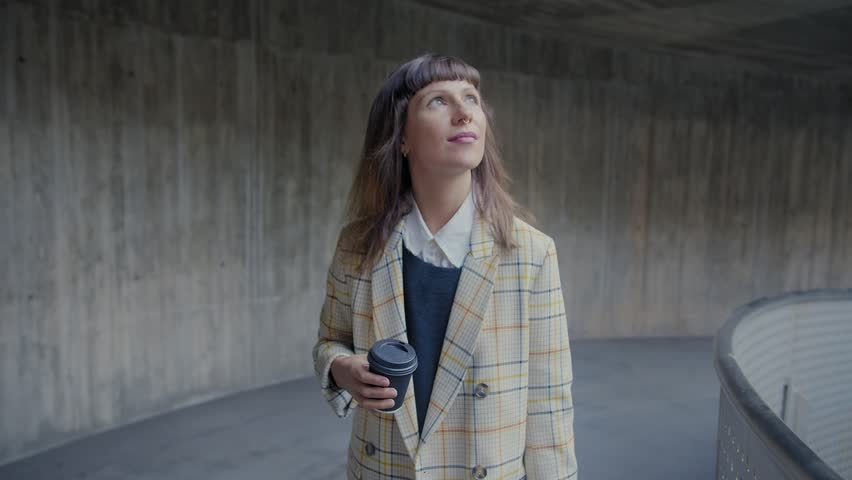 Young handsome pensive business woman walks around modern urban area, with take away cup, dressed in colorful suit, drinking hot coffee, looking at sunlight and thinking about future, concrete wall | Shutterstock HD Video #1026889070