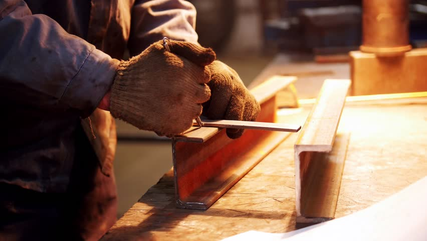 Construction plant. A worker making marks on an iron detail | Shutterstock HD Video #1026891068