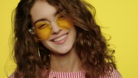 Young woman smiling on yellow background. Portrait of happy girl smiling in studio. Close up of fashion model smile. Happy woman in yellow sunglasses looking in camera