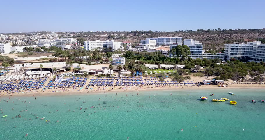 Aerial view of a holiday resort sandy beach, with beach umbrellas and sun beds. Crowded sandy beach in Ayia Napa Cyprus.