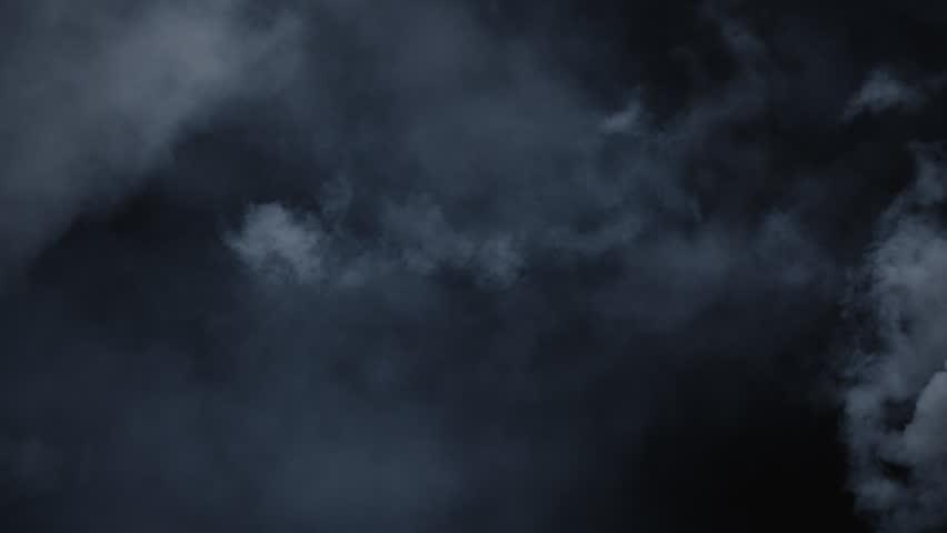 Atmospheric smoke VFX overlay element. Haze background. Smoke in slow motion on black background. White smoke slowly floating through space against black background. Mist effect. Fog effect.