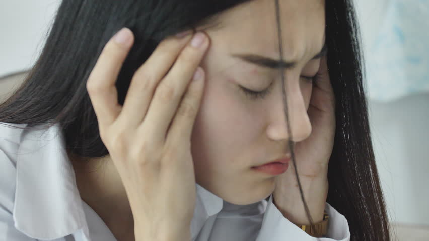 Asian woman feeling stress from work in the office.Tired business woman at workplace in office holding his head on hands feel headache. | Shutterstock HD Video #1026905750