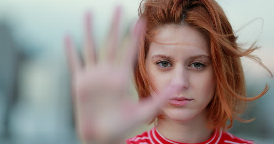 Redhead woman annoyed making stop sign with hand, saying no, expressing defense or restriction