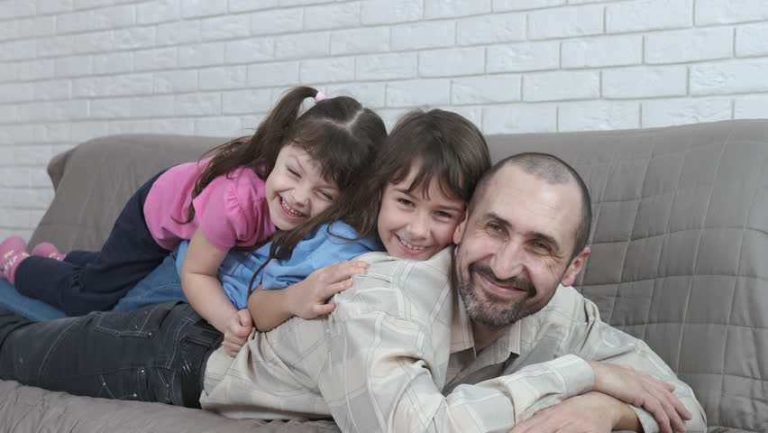 Portrait of a father with children. Daughters lie on dad. #1026921104