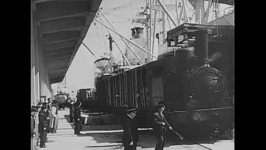 CIRCA 1950 - A train pulls out of a station and moves along the Italian countryside. Guards open a padlocked gate for it to enter.