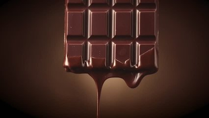 Chocolate bar with melted dark chocolate dripping over dark brown background. Confectionery concept backdrop. Melted premium chocolate flowing. Sweet dessert. 4K UHD video, slow motion