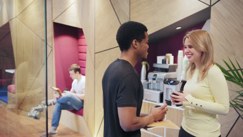 Two young professionals, African man and Caucasian woman, standing near espresso machine at office, drinking coffee and talking friendly at break #1026938102