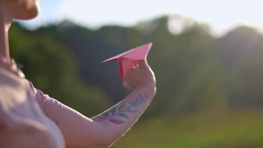A young, beautiful girl with a tattoo on her hand launches a paper airplane. Pretty woman, outdoors in nature, at sunset, launches a colored paper plane. | Shutterstock HD Video #1026947459