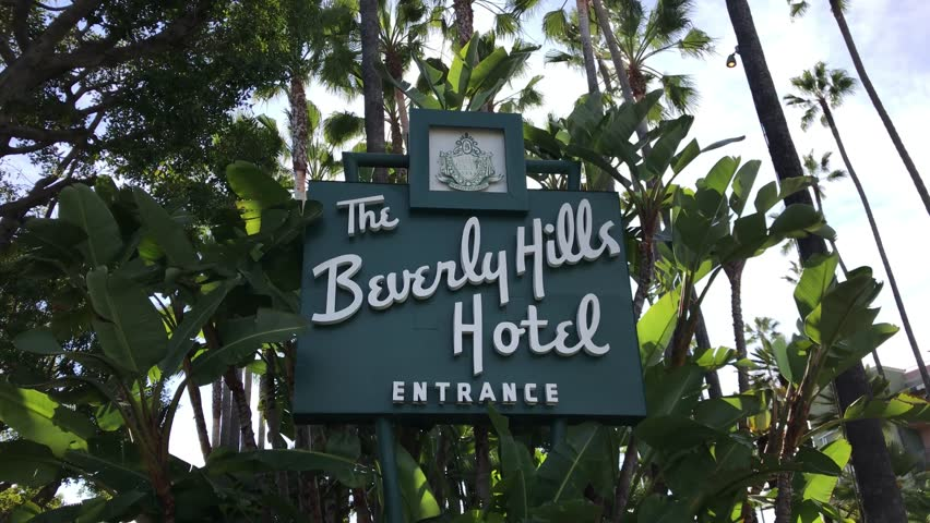 LOS ANGELES, March 30, 2019:Steady shot of the Beverly Hills Hotel entrance sign on Sunset Boulevard,surrounded by palms and a blue sky,then pan to car entering driveway. Sultan of Brunei is the owner