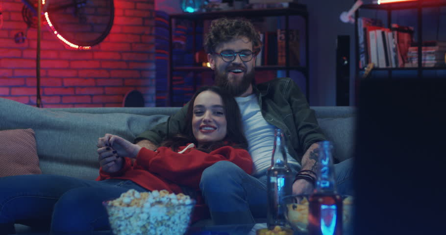 Pretty Caucasian young girl and handsome guy resting on the sofa at night, smiling and watching movie on TV.
