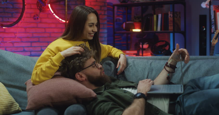 Attractive and happy Caucasian young girlfriend and boyfriend resting on the sofa with laptop computer at night, man lying on woman's laps while tapping and they looking on the screen. | Shutterstock HD Video #1026957992