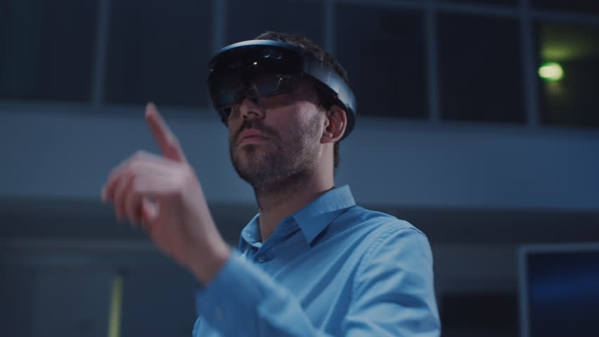 In 3D Content Creating Laboratory Engineer Wearing Professional Virtual Reality Headset Works and Gestures in Augmented Reality. Stylish Low Angle Arc Portrait Shot