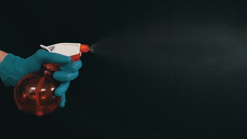 Hands in rubber gloves spray water out of the bottle | Shutterstock HD Video #1027000340