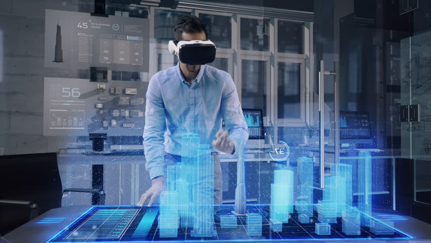 Professional Male Architect wearing Augmented Reality Headset makes gestures and redesigns 3D City Model. High Tech Office use Virtual Reality Modeling Software Application.